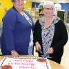 New head librarian Laurie Huestis and Sharon Edwards cut the retirement party cake.