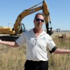 Fort Macleod Mayor Shawn Patience on the site of the Alberta Public Security and Law Enforcement Training Centre. In the background are buildings and equipment at the base camp of Bird Construction Co., which was awarded the contract by the province to build the training centre.