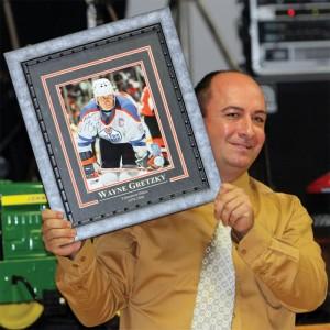 Brian Vandervalk displays a framed, autographed photo of hockey star Wayne Gretzky.auction.
