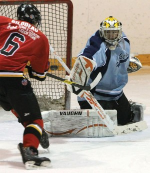 Tyler Bilodeau of the Fort Macleod Mustangs tries to knock the puck out of the air past Lomond Lakers goalie Michael-Lee Teslak.