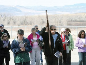 Doug McTrowe carries the cross as the procession moves along with a scenic background.
