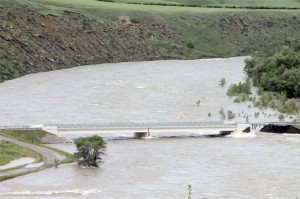 A portion of the bridge is washed out just downstream from the Oldman dam.