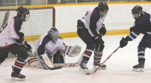 Fort Macleod Mavericks defenceman Cauy Yellow Face clears the puck from goalie Brody Zmurchyk's crease.
