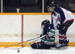 A Claresholm Thunder players is checked by Mavericks captain Ethan Grier.