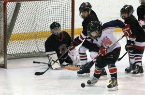 Nathan Keller of the Mavericks jumps on a loose puck in front of the Siksika goal.