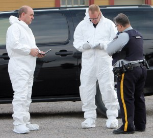 Cpl. Bryan Mucha (right) talks with members of the forensic team.