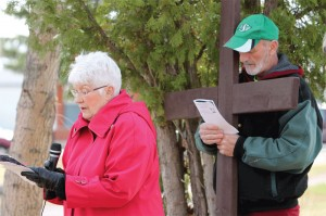 Dell Schmidt gives a reading at one of the Stations of the Cross, with Chris Adamiak holding the wooden cross.