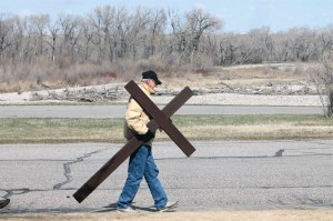 River Valley Wilderness Park is in the background as Doug McTrowe carries the cross on 27th Street.