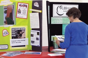 Doris Davis inspects the Family and Community Support Services display.