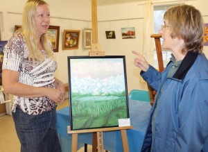 Fort Macleod Art Club member Dena Carlsen discusses one of her paintings with Evelyn McTrowe on Friday.