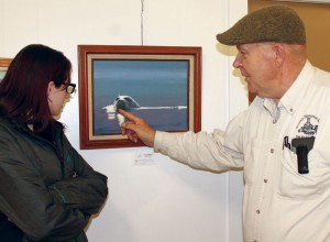Mary Jane Bohnet learns more about one of the paintings from artist Dwight Taylor.