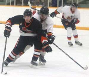 Quinn Costa of Wainwright tries to shield the puck from Darren Smith of Fort Macleod.