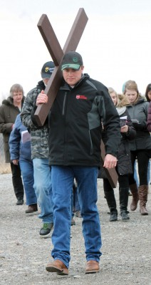 Travis Doyle carries the cross during the Way of the Cross procession on Good Friday in Fort Macleod.