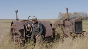 Sitting on one of his family's old tractors, Herb Pidt recalls the challenges and rewards of farm life (CONTRIBUTED)