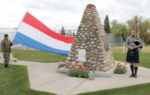 Lieut. Werner Dressler of the 2309 Fort Macleod Army Cadets holds the Dutch flag as the piper plays.