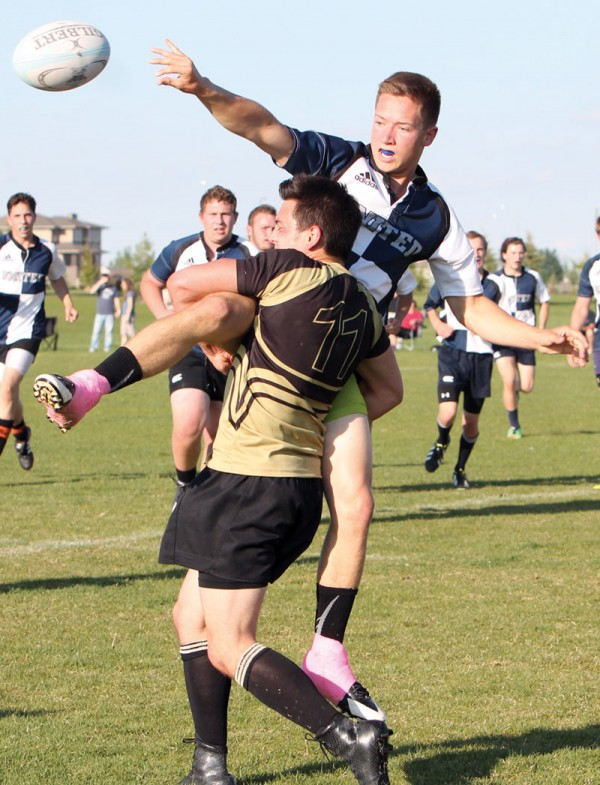 Aiden Seguin of United releases the ball as he is tackled by a Chinook Coyote.
