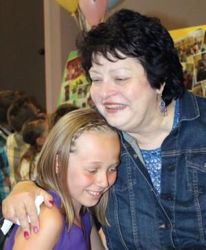 Retiring teacher Lori Filatoff gets a hug from one of the students.
