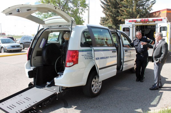 Non-ambulance transfer van driver Ron Lewison discusses the new vehicle with Fort Macleod Mayor Rene Gendre.