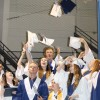 Members of the Class of 2016 toss their mortarboard caps into the air at the conclusion of the cap and gown ceremony.