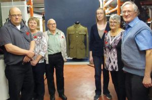 From right: Sgt. Jack Shield's grandson Michael Stonhouse, youngest daughter Edith Moyes, Edith's husband Sam Moyes, Ruthann LaBlance of the Galt Museum, granddaughter Susan Shores and grandson Jerry Ellerman stand around the tunic from World War One.