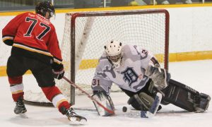 Ben Bohle (77) of the Fort Macleod Mustangs is stopped by Kainai Braves goalie Daylin Mistaken Chief.