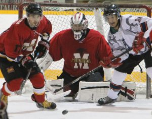 Fort Macleod Mustangs goalie Dean Skidmore does the butterfly behind Mustangs defenceman Taylor Bilodeau and Kainai's Ferguson Calf Robe.