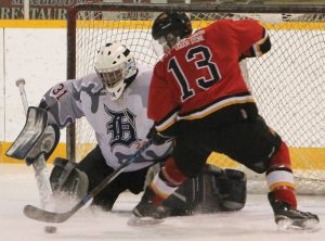 James Price (13) of the Fort Macleod Mustangs tries to jam the puck past Kainai Braves goalie Daylin Mistaken Chief.