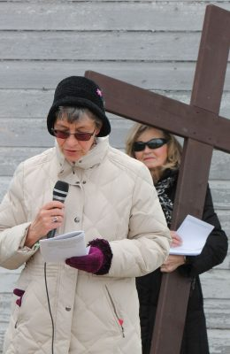 Pat Ness gives a reading as Laura Martin holds the wooden cross.