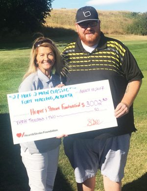 Fort Macleod Golf Club manager Shawn O'Sullivan presents a cheque to Trish York of the Heart and Stroke Foundation.