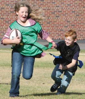 Rylee Lichtenberger runs with the ball as Cash Kroetsch dives for her flag in a game of rugby at W.A. Day school in Fort Macleod. Rugby is one of the programs offered in the Wolfpack Sports Academy.