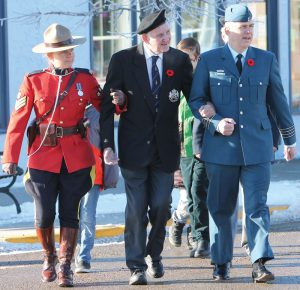 RCMP Sgt. Laura Akitt and Col. Stephane Guevremont assisted 94-year-old veteran Stan Edwards on the march from the cenotaph on Second Avenue to the community hall.