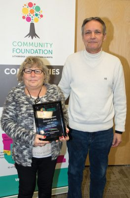 Anita Walker (left) of Granum Public Library accepted a $5,000 grant from Bob Short of the Community Foundation grants committee.